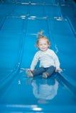 Bébé heureux sur la glissière colorée Photo stock