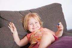 Bébé heureux sur le sofa Photographie stock libre de droits