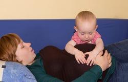 Bébé investissant son ventre enceinte de mères Photo stock