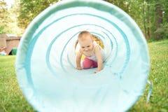 Bébé jouant à l'intérieur d'un tunnel de jouet Image stock