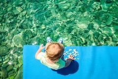 Bébé jouant avec des pierres par la mer images libres de droits