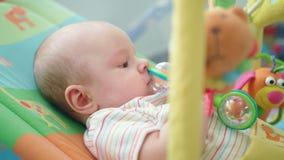 Bébé jouant avec le jouet Portrait d'enfant doux jouant avec le sac à haricots dans le lit clips vidéos
