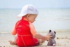 Bébé jouant avec le jouet sur la plage avec la mer sur le fond Concept pour l'amitié et l'enfance heureux Images libres de droits