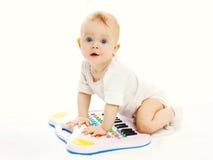 Bébé jouant avec le piano de jouet sur le fond blanc Photographie stock libre de droits