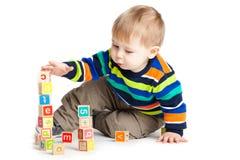 Bébé jouant avec les cubes en bois en jouet avec des lettres. photos stock