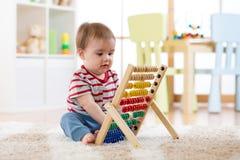 Bébé jouant avec un abaque apprenant à compter photos stock