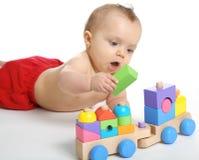 Bébé jouant avec un jouet en bois de train image stock