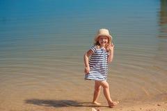 Bébé jouant dans l'eau à la plage Images stock