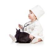 Bébé jouant le docteur avec le lapin d'animal familier photographie stock