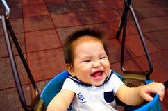 Bébé jouant sur une oscillation Photos libres de droits