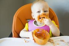 Bébé mangeant avec la nourriture sur le visage Photographie stock libre de droits