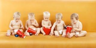 Bébé mangeant du maïs éclaté, groupe d'enfants regardant TV, enfants un an images libres de droits
