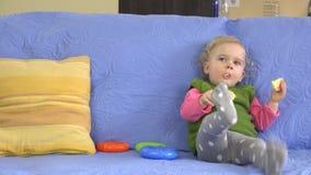 Bébé mangeant le biscuit de maïs se reposant sur le sofa bleu à la maison banque de vidéos