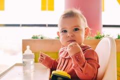 Bébé mangeant seule au highchair photo libre de droits