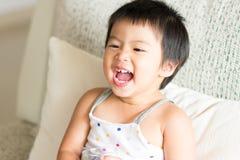 Bébé mignon asiatique souriant et tenant un verre de l'eau Conce photographie stock libre de droits