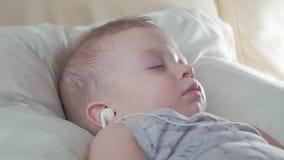 Bébé mignon avec des écouteurs dormant gentiment sur le lit à la maison clips vidéos