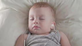 Bébé mignon avec des écouteurs dormant gentiment sur le lit à la maison banque de vidéos