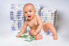 Bébé mignon avec l'argent sur le fond trouble de couches-culottes Photo stock