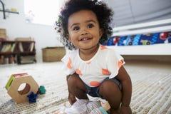 Bébé mignon ayant l'amusement dans la salle de jeux avec des jouets photo stock