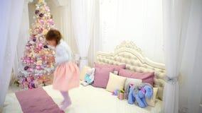 Bébé mignon ayant l'amusement et sautant sur le lit chez la pièce du ` s des enfants sur l'arbre de Noël rose de fond avec des jo clips vidéos