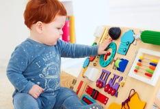 Bébé mignon d'enfant en bas âge jouant avec le conseil occupé à la maison Photo libre de droits