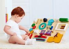 Bébé mignon d'enfant en bas âge jouant avec le conseil occupé à la maison Photos libres de droits