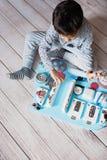 Bébé mignon d'enfant en bas âge jouant avec le conseil occupé à la maison Photographie stock