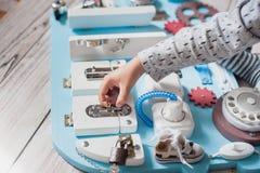 Bébé mignon d'enfant en bas âge jouant avec le conseil occupé à la maison Photo stock