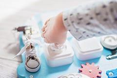 Bébé mignon d'enfant en bas âge jouant avec le conseil occupé à la maison Images stock