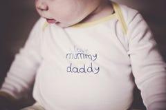 Bébé mignon dans l'habillement léger avec de mots les I ` de maman et de papa d'amour du ` Imitation de grain de film Photo stock