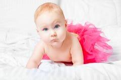 Bébé mignon dans la jupe rose avec des yeux bleus au-dessus de la couverture blanche photos stock