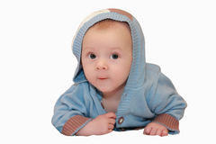 Bébé mignon dans le chandail avec le capot se trouvant sur son estomac d'isolement sur le blanc Photos stock