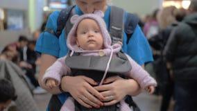 Bébé mignon dans le transporteur de kangourou de mères banque de vidéos