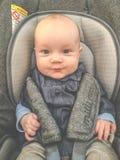 Bébé mignon dans un siège de voiture de manière de Milli images stock