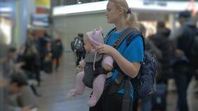 Bébé mignon dans un transporteur de bébé à l'aéroport banque de vidéos