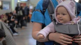 Bébé mignon dans un transporteur de bébé à l'aéroport clips vidéos