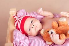 Bébé mignon dormant dans le lit avec l'ours de nounours Photo libre de droits