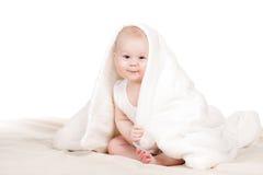 Bébé mignon jetant un coup d'oeil de dessous la couverture Photographie stock libre de droits
