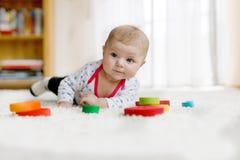 Bébé mignon jouant avec le jouet en bois coloré de hochet Photographie stock libre de droits