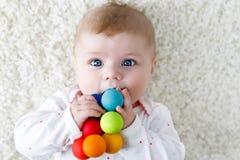 Bébé mignon jouant avec le jouet en bois coloré de hochet Photos stock