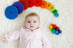 Bébé mignon jouant avec le jouet en bois coloré de hochet Photographie stock