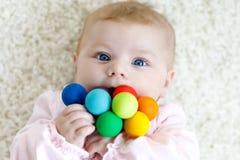 Bébé mignon jouant avec le jouet en bois coloré de hochet Images stock