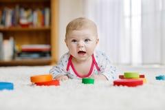 Bébé mignon jouant avec le jouet en bois coloré de hochet Photo stock