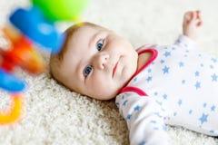 Bébé mignon jouant avec le jouet en bois coloré de hochet Image libre de droits