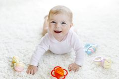 Bébé mignon jouant avec le jouet en pastel coloré de hochet de vintage Photographie stock