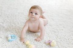 Bébé mignon jouant avec le jouet en pastel coloré de hochet de vintage Image libre de droits