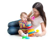 Bébé mignon jouant avec sa mère d'isolement sur le fond blanc Image stock