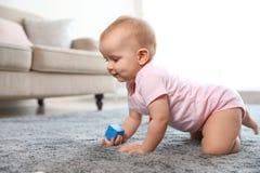 Bébé mignon jouant sur le plancher dans la chambre images libres de droits