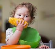 Bébé mignon mangeant du maïs photo stock