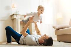 Bébé mignon positif se sentant heureux tout en étant dans les bras du père Photos stock
